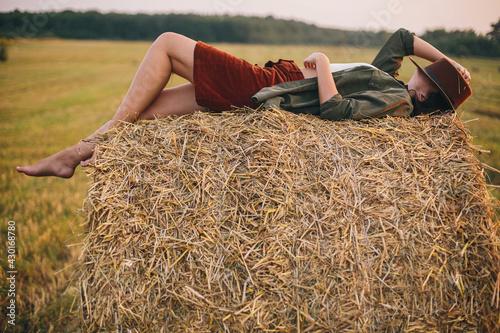Fototapeta Beautiful carefree woman lying on haystack enjoying evening in summer field