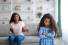 Little Black Girl Feeling Unhappy And Offended, Being Scolded By Her Angry Tired Mother At Home, Blank Space