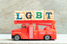 Fire Ladder Truck Hold Letter Block In Word LGBT (Abbreviation Of Lesbian, Gay, Bisexual, And Transgender) On Wood Background