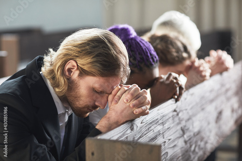 Fototapeta Group of people sitting in a row with eyes closed and praying together in the church obraz
