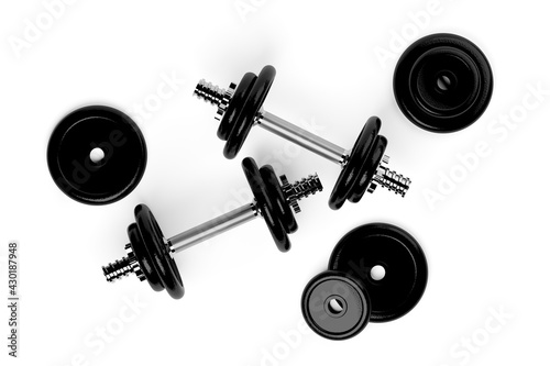 Fototapeta premium Two fitness gym dumbbells with chrome handle and black plates over white background flat lay top view from above, muscle exercise, bodybuilding or fitness concept