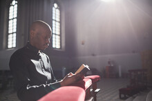 African Priest Sitting In Front Of The Altar And Reading The Bible In The Church