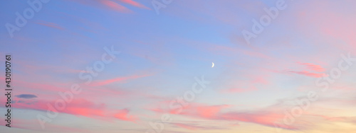 Clear blue sky, glowing pink and golden clouds after storm at sunset. Dramatic cloudscape. Moon, moonrise, midnight sun. Concept art, meteorology, heaven, hope, peace, picturesque panoramic scenery