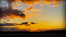 Beautiful Orange Sunset Over An Agricultural Field With Tree Silhouettes On The Horizon