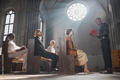 Fotografie, Tablou African young priest reading the Bible for faithful people while they sitting on