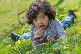 Fototapeta Dmuchawce - Little boy hunting for Easter egg in spring garden on Easter day.