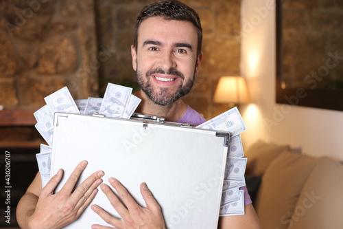 Fototapeta Man holding briefcase full of cash