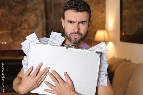 Obraz na plátně Man holding briefcase full of cash