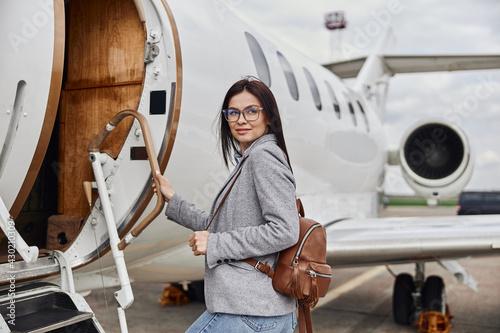 Fotografia Happy caucasian beautiful dark hair businesswoman is boarding a private jet