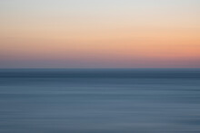 Beautiful Long Exposure Landscape Image Of Calm Sea And Colorful Sunset Sky