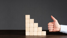 Wooden Cubes On The Table Are Stacked In A Pyramid. Hand With A Raised Thumb Up. Profit Growth Protection Concept. Business Idea.