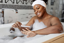 Portrait Of Nice Good-looking African Lady Sawing Nails While Taking Bath, Close-up Hands
