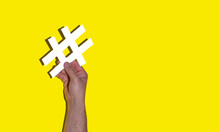 Man's Hand Holding A White Hash On A Yellow Background - Social Media Day Concept