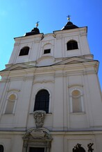 Front View Of Twin Tower From Late Baroque Religious Building Of Church Of Holy Trinity In Trnava, Western Slovakia, Built In Year 1729 By Trinitarians Order. Late Spring Clear Day With Blue Skies.