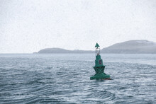 Green Buoy With Cone Shaped Topmark Under Snow