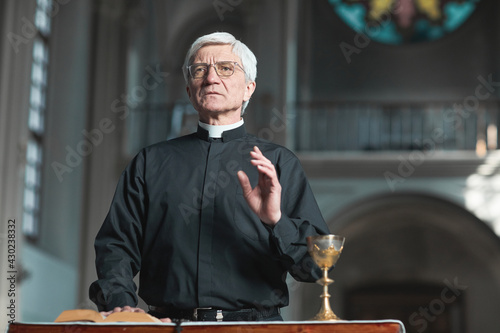 Fotografia Senior priest standing at the altar and praying while serving in the church
