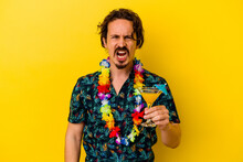 Young Caucasian Man Wearing A Hawaiian Necklace Holding A Cocktail Isolated On Yellow Background Screaming Very Angry And Aggressive.