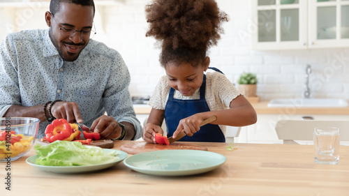 Canvas Print Happy African American daughter kid helping dad to prepare dinner, slicing vegetables, fresh pepper for salad on kitchen table