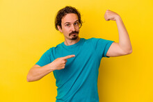 Young Caucasian Man Isolated On Yellow Background Showing Strength Gesture With Arms, Symbol Of Feminine Power