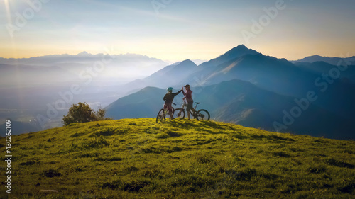 Two happy woman high five over the sunset after a successful mountain biking trip in the mountains. Celebrate a cross country cycling journey. - fototapety na wymiar