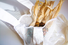 Colored Bright Corn In A Shopping Mesh Bag. Fancy Food, Dry Popcorn Product. White String Bag On A White Table On A Bright Sunny Day.