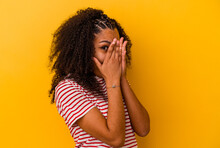 Young African American Woman Isolated On Yellow Background Blink Through Fingers Frightened And Nervous.