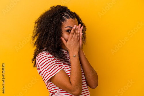 Canvas Print Young african american woman isolated on yellow background blink through fingers frightened and nervous