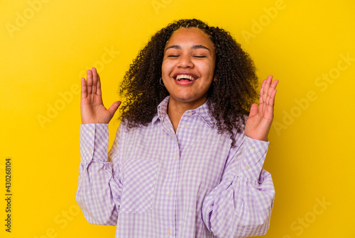Vászonkép Young african american woman isolated on yellow background laughs out loudly keeping hand on chest