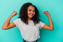 Young African American Woman Isolated On Blue Background Showing Strength Gesture With Arms, Symbol Of Feminine Power