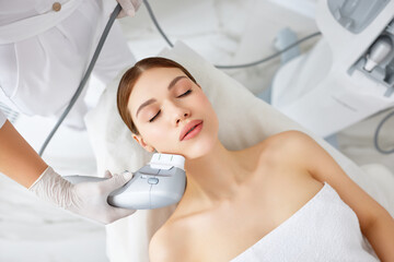 Woman getting facial lifting therapy in beauty salon