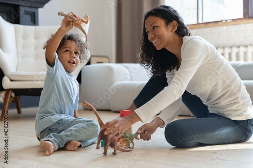 Naklejka premium Happy cute kid boy and his mom relaxing on heat floor in cozy living room and playing with small dinosaurs figures together. Mother engaged in little sons game with toys. Family playtime concept