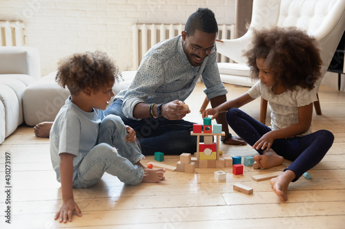 Happy daddy and two engaged preschooler kids building tower from toy wooden blocks on heat floor Fototapet