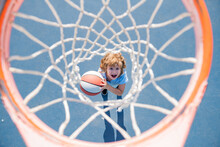 Amazed Kid Playing Basketball Holding Ball With Happy Face.