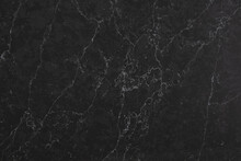 Closeup Of A Dark Marble Looking Quartz Slab That Contains A Two-toned Charcoal Grey Background With Soft Light Grey Subtle Veins