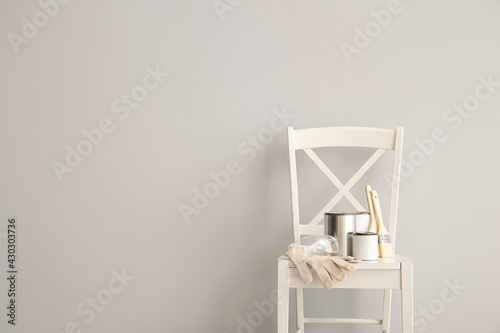 Fototapeta Chair with cans of paints and tools near light wall obraz