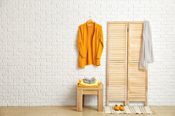 Folding screen and table with stylish clothes in modern room