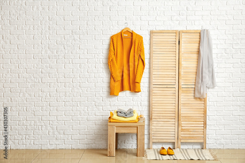 Folding screen and table with stylish clothes in modern room - fototapety na wymiar