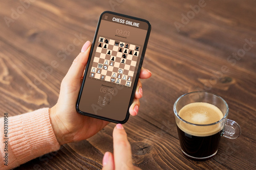Photo Person playing chess online on mobile phone