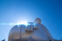 Back Big Silver Buddha Statue On Blue Sky Background . Wat Roi Phra Phutthabat Phu Manorom Mueang Mukdahan District, Mukdahan Province, Thailand. Copy Space