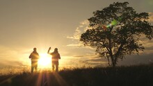 Silhouette Of Two Travelers Walking Through The Field Past A Lonely Tree In The Sun. Teamwork Of Tourists With Backpacks In The Sun. Hiking And Adventure Concept. Business And Cooperation, Partners
