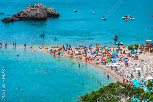 Crowds of people enjoying the sunshine / sunbathing  on a tiny strip of sand at Isola Bella beach - the most beautiful summer destination in Sicily, Italy - fototapety na wymiar