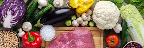 Fototapeta Fresh farm organic vegetables banner, healthy food concept, vegetables and mushrooms, superfoods and beans around the board with a large fresh piece of beef fillet, top view obraz