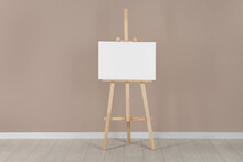 Wooden Easel With Blank Canvas Near Beige Wall