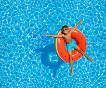 Boy Swim In Pool On Inflatable Ring From Above