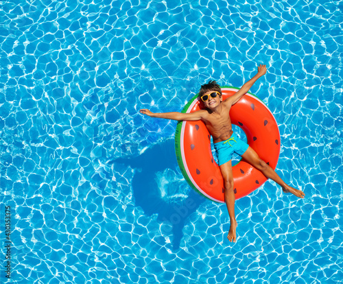 Fotografia Boy swim in pool on inflatable ring from above