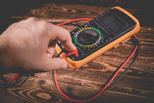 Multimeter And Two Test Leads On A Wooden Background. A Man's Hand Holds Two Test Leads. A Studio Photo With Hard Lighting.