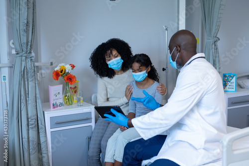 Diverse mother, ill daughter and male doctor using tablet sit on hospital bed, wearing face masks