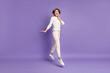 Leinwandbild Motiv Full length body size photo of happy girl bob hair jumping touching cheek smiling isolated on pastel purple color background