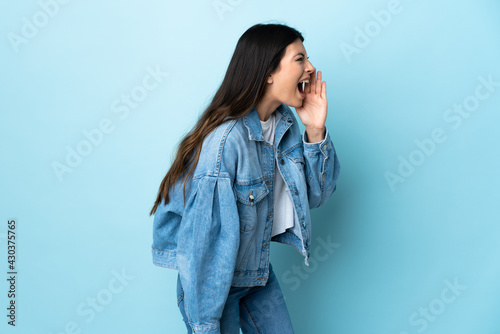 Obraz na plátně Young brunette girl over isolated blue background shouting with mouth wide open