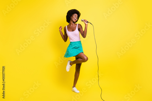 Fototapeta Full body photo of dark skin attractive girl wear pink singlet hold sing microphone isolated on yellow color background obraz